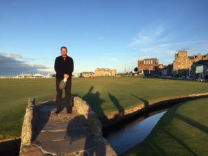 Jim stopping for the iconic Old Course photo under blue skies.